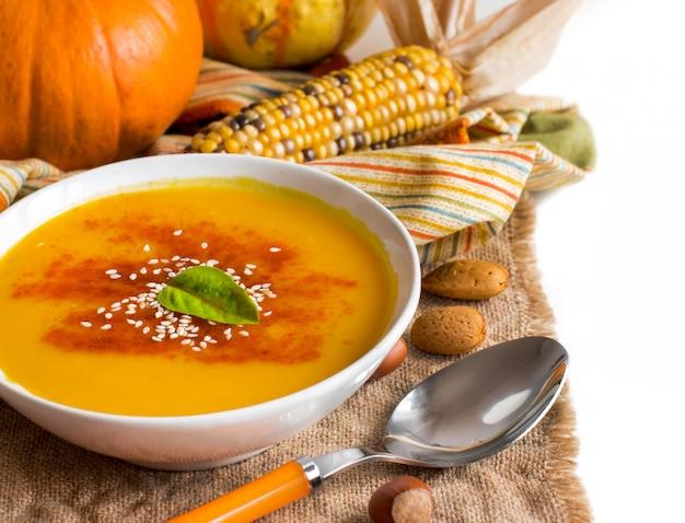 Sopa fresca de abóbora com colher e vegetais close-up