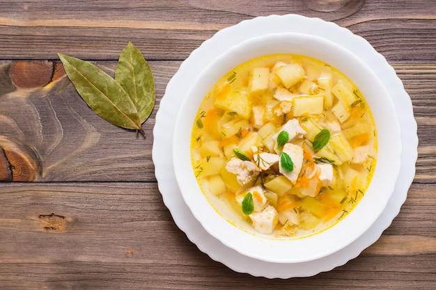 Sopa fresca de caldo de galinha com batatas e ervas em uma tigela branca e louro em uma mesa de madeira. vista do topo