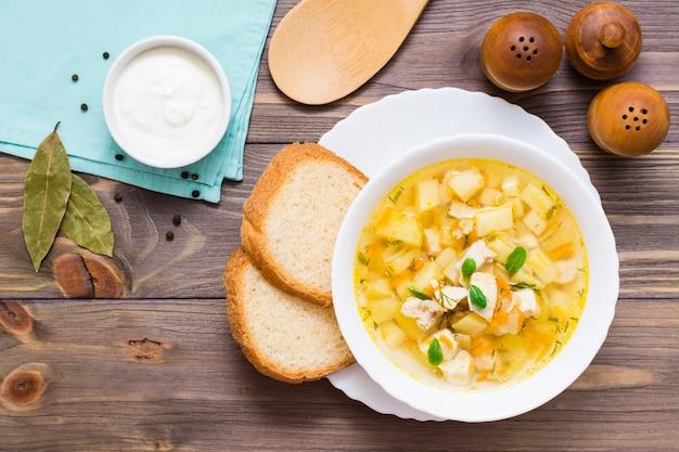 Sopa fresca do caldo de galinha com batatas e ervas em uma bacia branca em uma tabela de madeira.