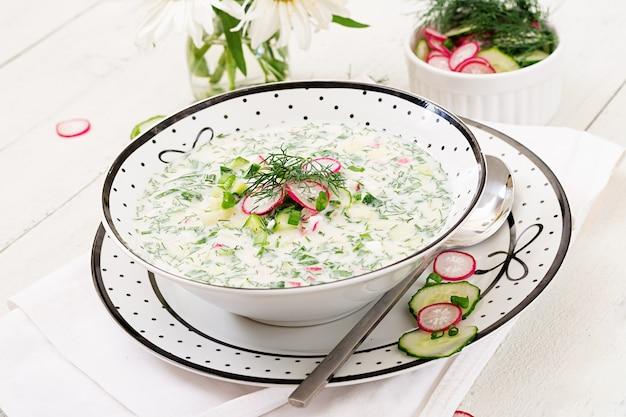 Sopa fria com pepinos frescos, rabanetes com iogurte na bacia no fundo de madeira.