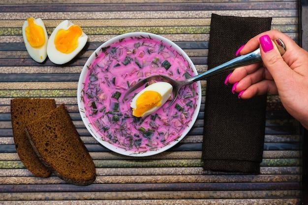 Sopa fria de beterraba com ovos em uma colher na mão e pão em uma bandeja decorativa