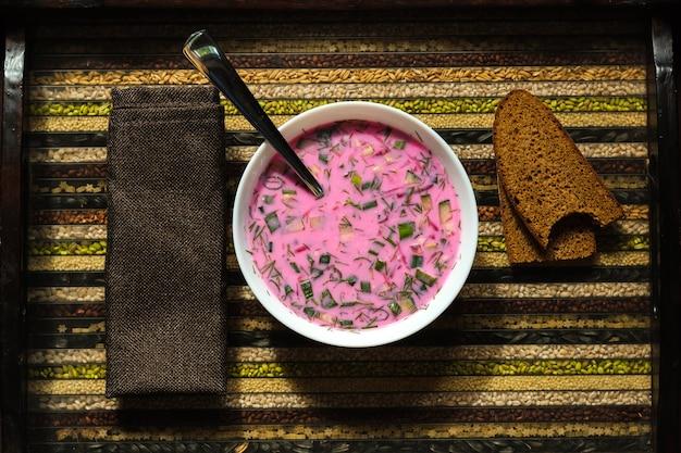 Sopa fria de beterraba em uma colher na mão e pão em uma bandeja decorativa
