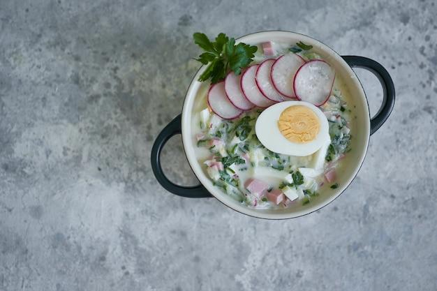 Sopa fria de okroshka russa tradicional servida em um prato com ervas e ovo sopa de vegetais kefir