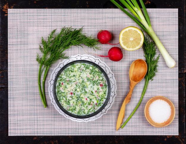Sopa fria de verão russo okroshka de legumes, kvass e kefir com verdes em cima da mesa