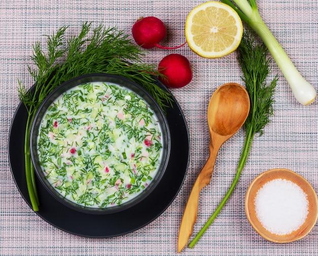 Sopa fria de verão russo okroshka de verduras, legumes, kvass e kefir em cima da mesa