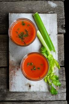 Sopa gaspacho - sopa de tomate espanhol em copos, ingredientes em madeira rústica