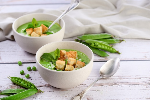 Sopa gelada de purê de ervilhas, temperada com cebolinha, hortelã e pão torrado crocante torrado em cubos