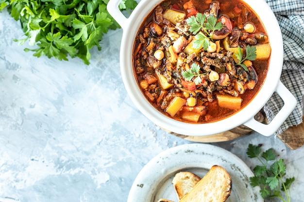 Sopa grossa de carne picada com tomate, feijão, grão de bico e legumes.