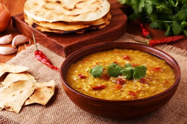 Sopa grossa de lentilha vermelha indiana com coentro, servida com pão indiano achatado em um fundo de madeira.