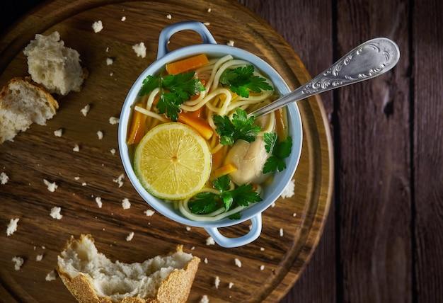 Sopa italiana com espaguete, cenoura, limão, salsa e pedaços de frango em um prato azul, em um carrinho de madeira e pão ao redor.