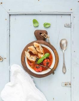 Sopa italiana de tomate, alho e manjericão pappa al pomodoro na tigela de metal com pão na placa de madeira rústica sobre luz azul.