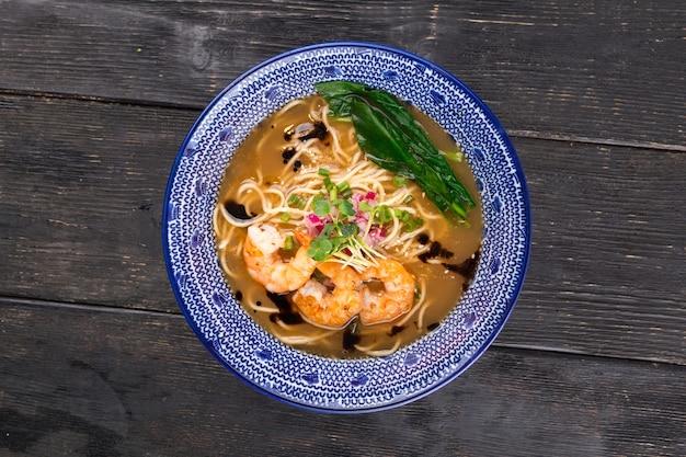 Sopa japonesa de macarrão ebi ramen com camarões tigre na mesa de madeira
