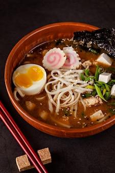 Sopa japonesa dos ramen com macarronetes, ovo, tofu, nori, em um prato japonês.