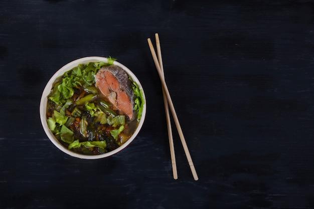 Sopa japonesa tradicional com algas wakame, legumes e salmão