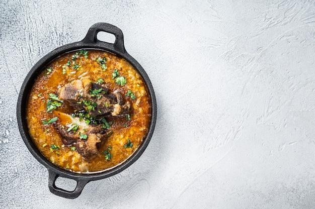 Sopa kharcho com carne bovina, arroz, tomate e temperos em uma panela. fundo branco. vista do topo. copie o espaço.