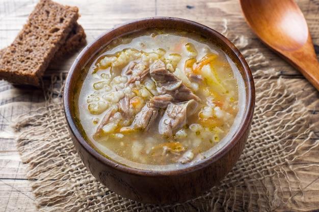 Sopa kharcho com carne e arroz na mesa de madeira