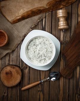 Sopa local dovga em iogurte com ervas dentro de tigela branca.