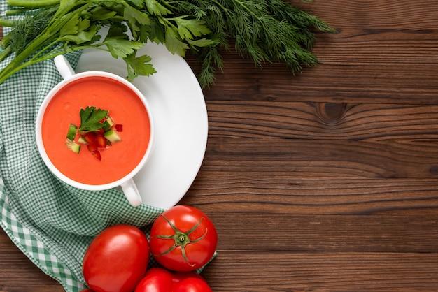 Sopa maravilhosa de gaspacho de tomate com ervas e tomates. vista do topo. copie o espaço.