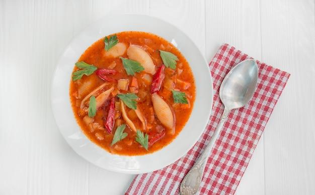 Sopa minestrone com macarrão e ervas. comida italiana. refeições quentes. prato vegetariano. mesa de jantar. fundo de madeira branco. fechar-se.
