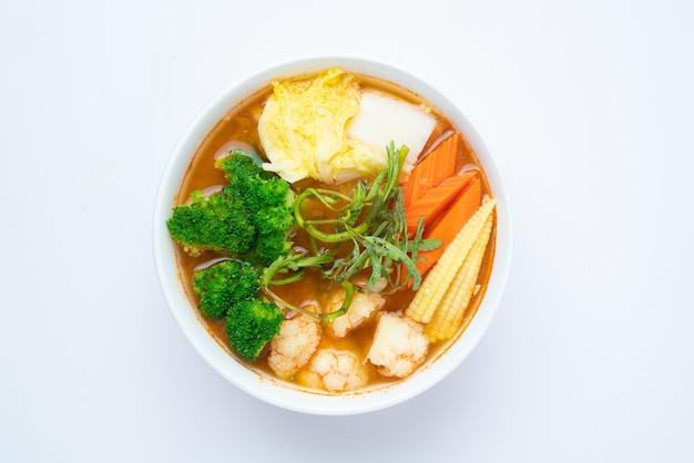 Sopa mista de vegetais em azedo feita de pasta de tamarindo com camarão e omelete de vegetais - estilo de comida asiática ou comida tailandesa isolada