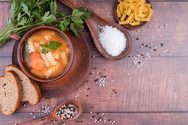 Sopa na tigela com pão e copie o espaço