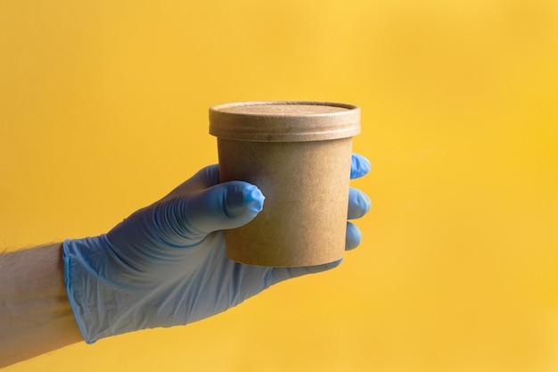 Sopa ou café em um copo descartável de papel para entrega de comida na mão de um homem em uma luva sobre um fundo amarelo.
