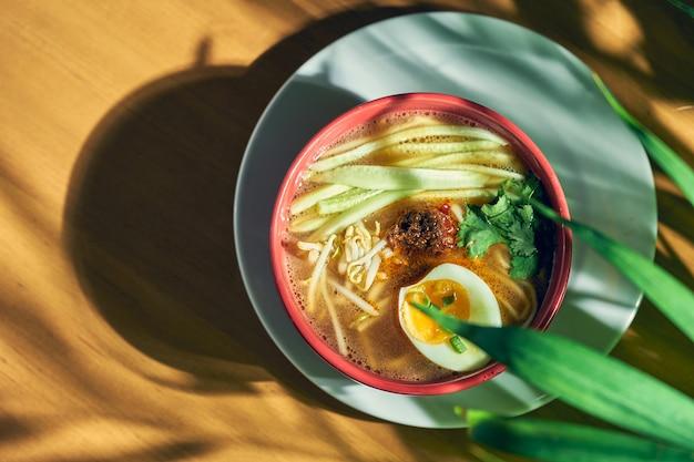 Sopa picante asiática de sichuan com macarrão, carne picada, ovo e pepino em uma tigela.