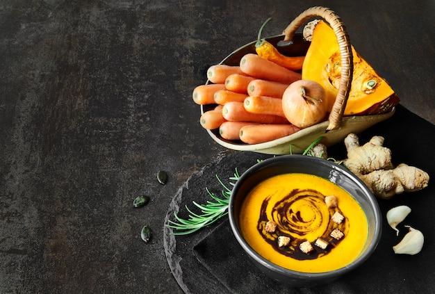 Sopa picante de abóbora e cenoura com gengibre, alho, cebola e pimentão no escuro
