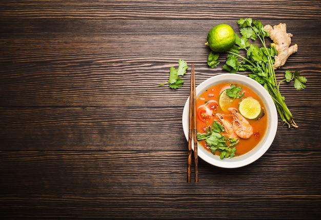 Sopa picante tradicional tailandesa quente fresca tom yum com camarão, limão e coentro em uma tigela sobre fundo de madeira rústico