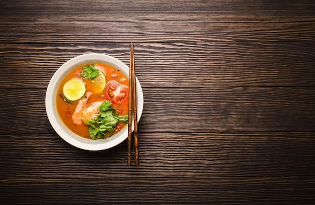 Sopa picante tradicional tailandesa quente fresca tom yum com camarões em uma tigela sobre fundo de madeira rústico