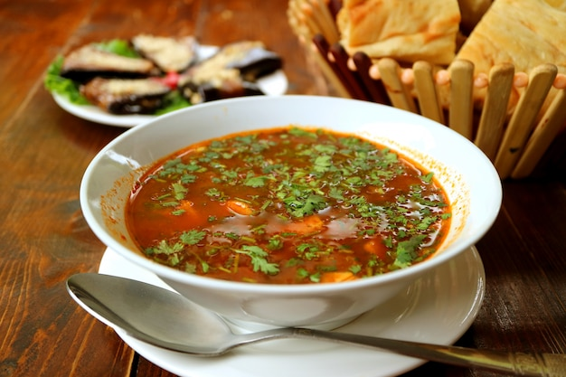 Sopa quente de carne da geórgia khashi com pão embaçado e rolos de berinjela no fundo