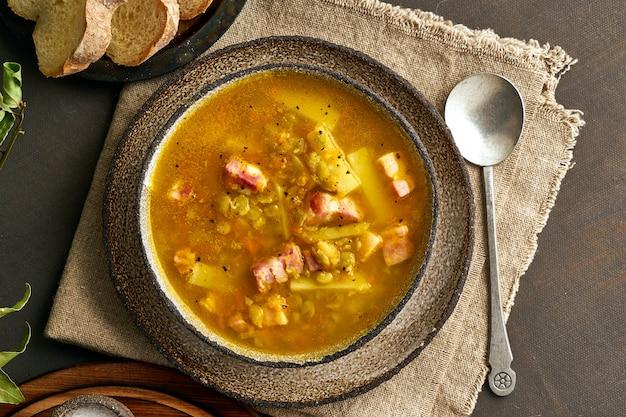 Sopa quente de inverno com ervilhas verdes picadas, carne de porco, bacon, fumado na mesa de madeira marrom escura