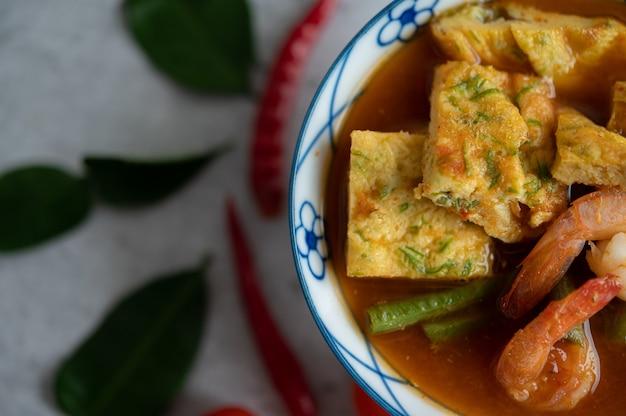 Sopa quente e azeda com cha-om, ovo e camarão em uma tigela branca, com pimenta e folhas de lima kaffir na superfície branca.