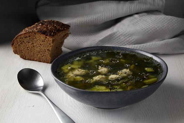 Sopa rústica de abobrinha com almôndegas com um pedaço de pão preto com sementes de cominho em uma mesa branca contra o fundo de um pano de prato cinza na luz da manhã