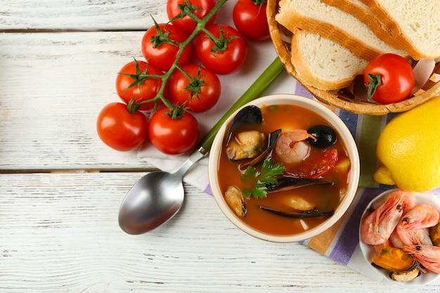 Sopa saborosa com camarões, mexilhões, tomates e azeitonas pretas em uma tigela com fundo de madeira