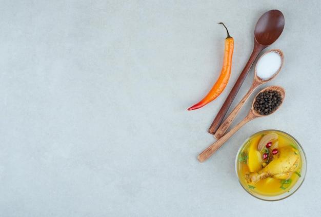 Sopa saborosa com especiarias e pimenta na mesa branca.