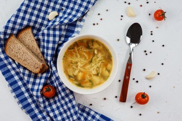 Sopa saborosa com macarrão e batatas, pedaços de pão na mesa branca.