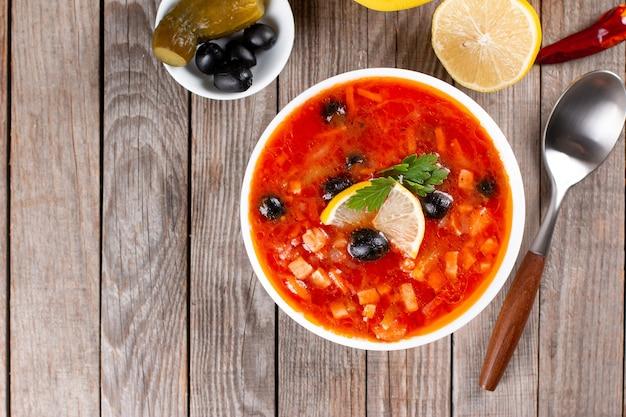 Sopa solyanka com linguiça, azeitonas, pepino em conserva e alcaparras