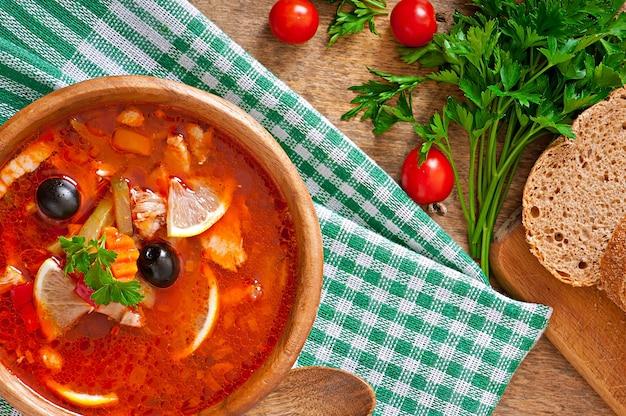 Sopa solyanka russo com carne, azeitonas e pepinos em uma tigela de madeira