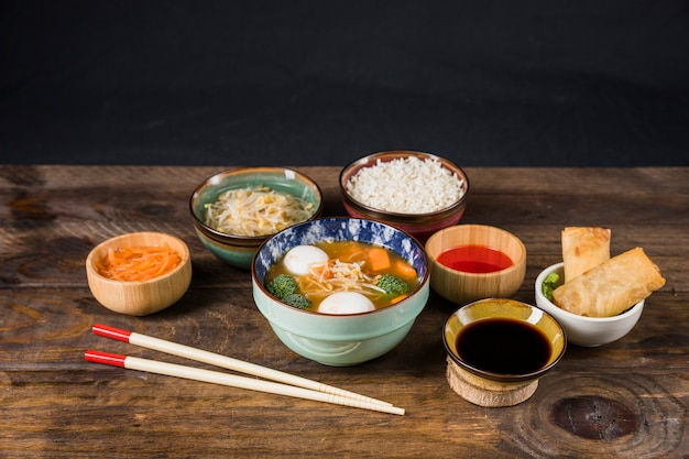 Sopa tailandesa; arroz; molho; broto de feijão; salada e rolinhos primavera fritos na mesa contra parede preta