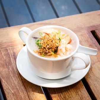Sopa tailandesa de arroz com camarões na mesa do café tailandês
