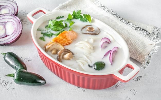 Sopa tailandesa de coco e salmão com ingredientes planos
