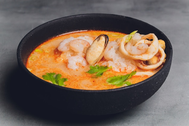 Sopa tailandesa picante tom yam com leite de coco, pimenta e camarão de frutos do mar e salmão em um prato sobre um fundo preto. cozinha asiática, menu do restaurante.