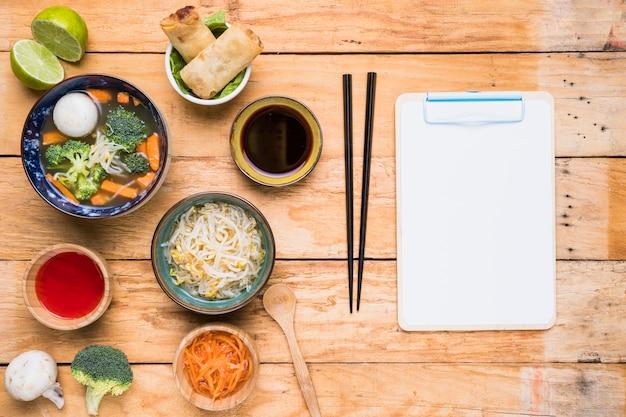 Sopa tailandesa; rolinho primavera; molhos e broto de feijão com pauzinho e papel branco na área de transferência sobre a mesa de madeira
