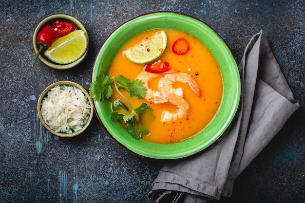 Sopa tailandesa saudável tradicional tom yum com camarão, limão, coentro em uma tigela sobre fundo rústico com arroz branco, tiro aéreo. conceito de comida tailandesa autêntica