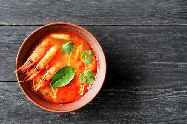 Sopa tailandesa tom inhame com camarão, limão e limão em uma vista superior da mesa de madeira.