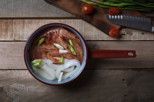 Sopa tailandesa tradicional tom yam na mesa de madeira