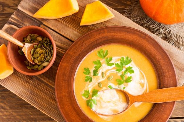 Sopa tradicional de abóbora sazonal em uma mesa de madeira em um prato com uma colher de pau. estilo rústico.
