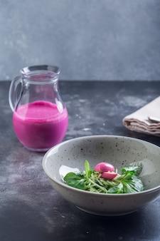 Sopa tradicional de beterraba fria de verão com legumes em uma tigela branca.
