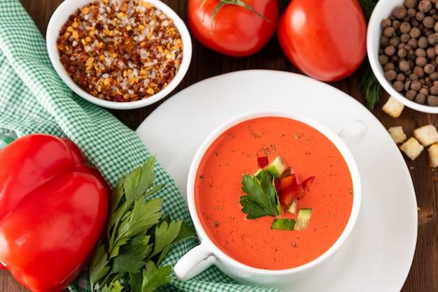 Sopa tradicional de tomate em um fundo de madeira com vista superior de diferentes temperos e ervas.